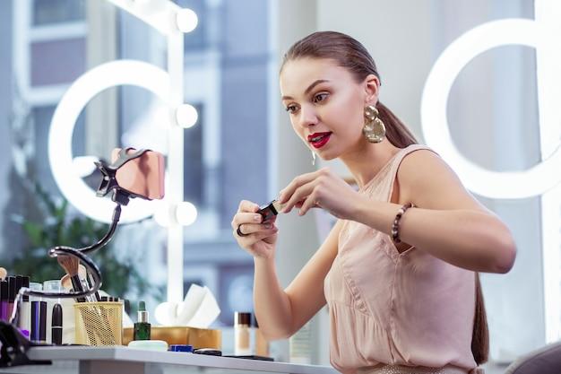 Ładna młoda kobieta siedzi przed kamerą podczas testowania kosmetyków