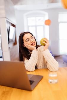 Ładna młoda kobieta siedzi w kuchni i pracuje na swoim laptopie i telefonie komórkowym