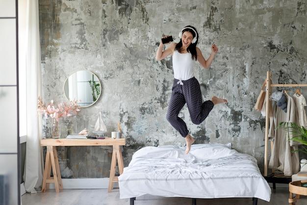Ładna młoda kobieta skacze w łóżku