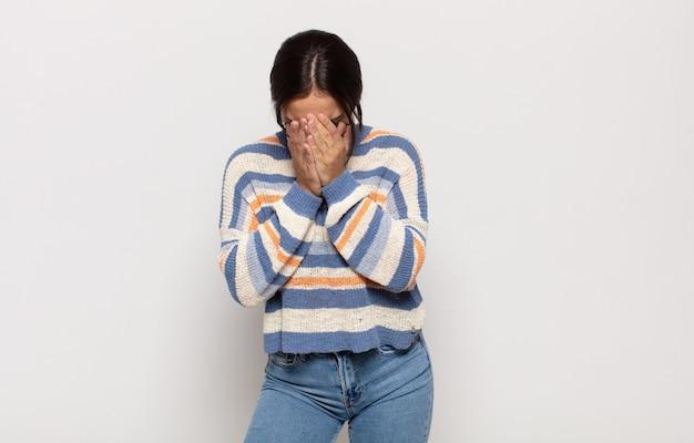 Ładna młoda kobieta smutna, sfrustrowana, zdenerwowana i przygnębiona, zakrywająca twarz obiema rękami, płacząca