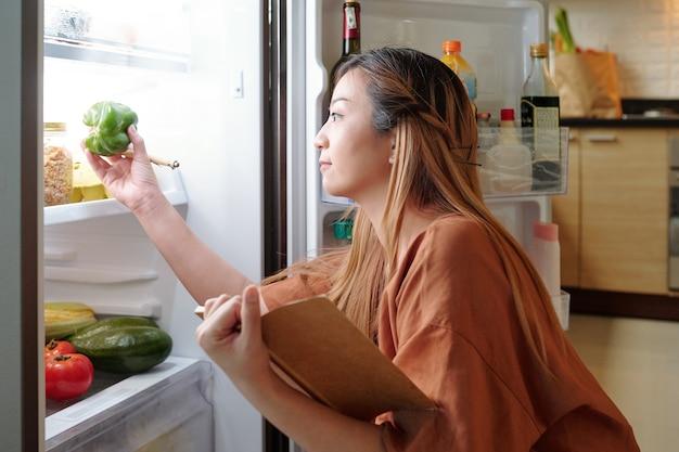 Ładna młoda kobieta sprawdza warzywa na półkach w lodówce podczas robienia listy zakupów