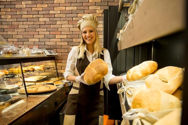 Ładna młoda kobieta sprzedaje świeżego chleb w piekarni