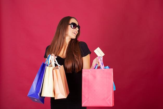 Ładna młoda kobieta stylowo ubrana na czarno z torbami po zakupach