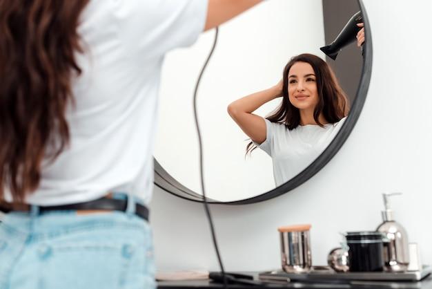 Ładna młoda kobieta suszy swoje piękne włosy i patrzy w lustro