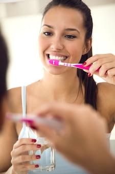 Ładna młoda kobieta szczotkuje jej zęby w łazience.