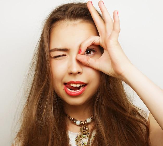 Ładna młoda kobieta szuka czegoś z szeroko otwartymi oczami i wyimaginowaną lornetką.