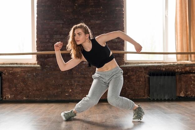 Ładna młoda kobieta tańczy w studiu tańca