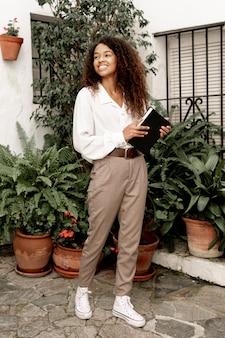Ładna młoda kobieta trzyma książkę outside