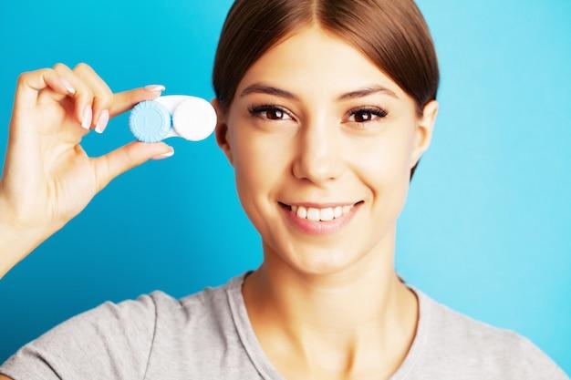 Ładna młoda kobieta trzyma pojemnik z soczewkami kontaktowymi dla wzroku