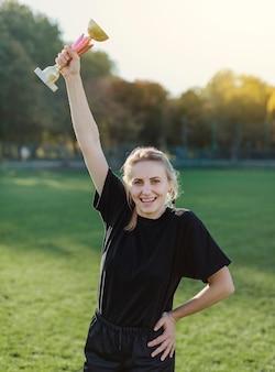 Ładna młoda kobieta trzyma trofeum