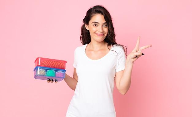 Ładna młoda kobieta trzyma tupperware