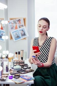 Ładna młoda kobieta trzymająca butelkę z błyszczącym cieniem do powiek podczas robienia jej zdjęcia