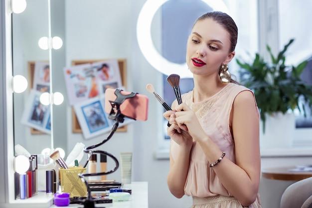 Ładna młoda kobieta trzymająca dwa pędzle do makijażu podczas nagrywania wideo na swoim blogu
