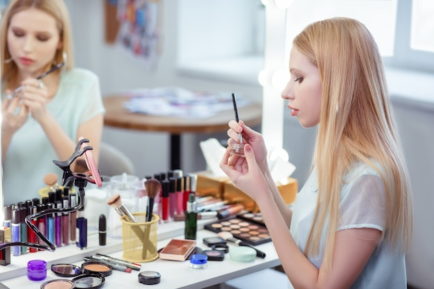 Ładna młoda kobieta trzymająca mały pędzelek podczas nakładania eyelinera