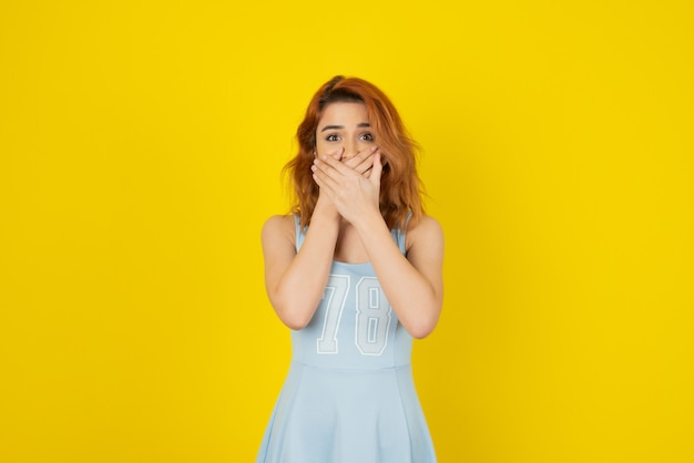 Ładna młoda kobieta trzymająca ręce przy ustach