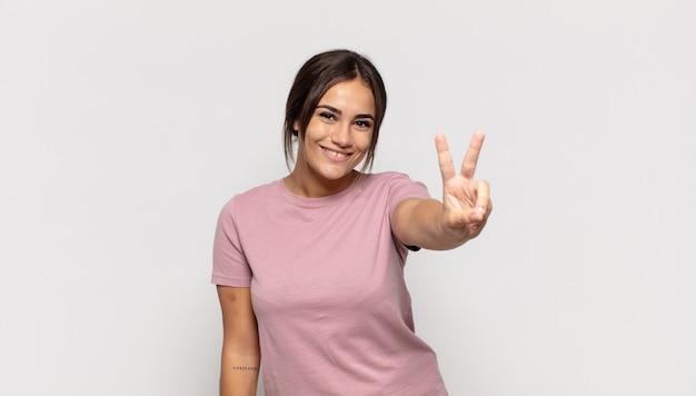 Ładna młoda kobieta uśmiechnięta i wyglądająca na szczęśliwą, beztroską i pozytywną, gestykulującą jedną ręką zwycięstwo lub pokój