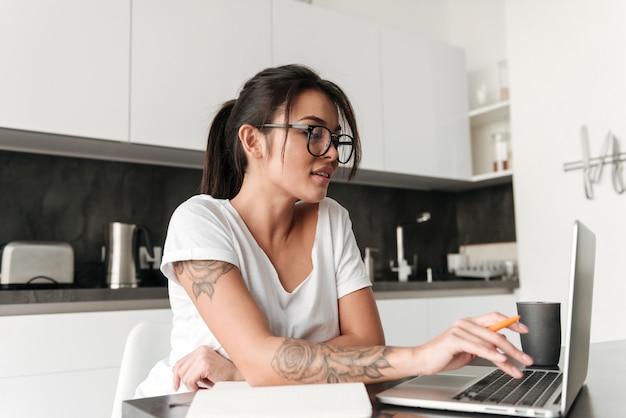 Ładna młoda kobieta używa laptop.
