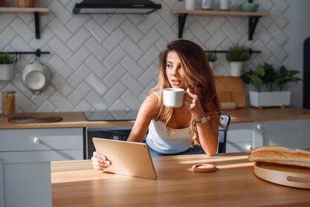 Ładna młoda kobieta używa pastylkę podczas gdy pijący ranek kawę po śniadania na kuchni.