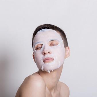 Ładna młoda kobieta używa twarzy maskę