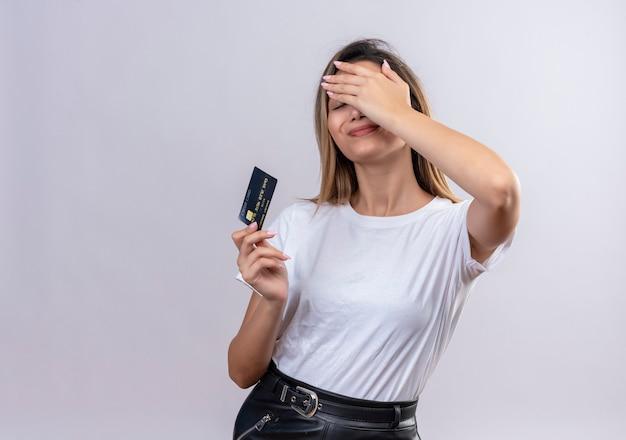 Ładna młoda kobieta w białej koszulce pokazuje kartę kredytową, trzymając rękę na czole na białej ścianie