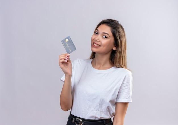 Ładna młoda kobieta w białej koszulce przedstawiającej kartę kredytową na białej ścianie