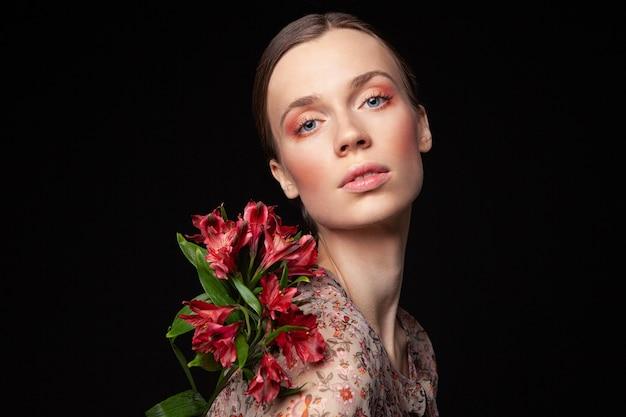 Ładna młoda kobieta w eleganckiej czerwonej bluzce dotykająca twarzy z naturalnymi kwiatami i odwracająca wzrok na czarnym tle