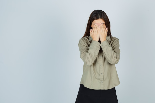 Ładna młoda kobieta w koszuli, spódnica zakrywająca twarz rękami i patrząc na depresję, widok z przodu.