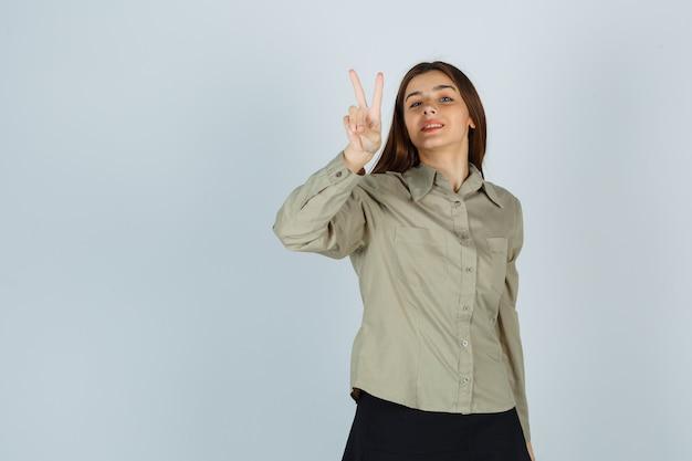 Ładna młoda kobieta w koszuli, spódnicy pokazując gest zwycięstwa i patrząc wesoło, widok z przodu.