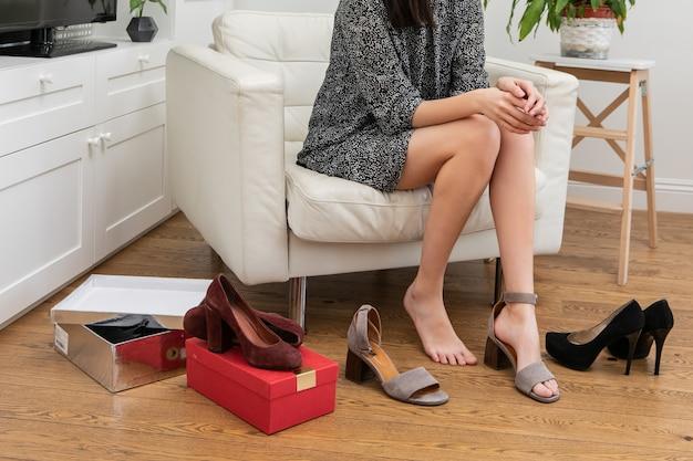 Ładna młoda kobieta w krótkiej sukience siedzi na krześle w salonie obok szafy i wybiera dziś buty do noszenia. dziewczyna przymierza buty na wysokich obcasach. pojęcie zakupów internetowych