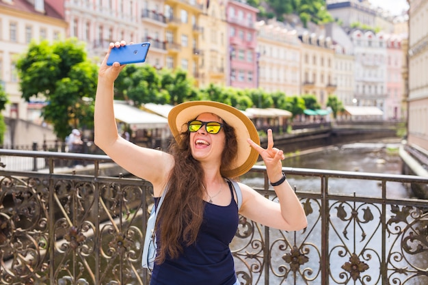 Ładna młoda kobieta w okularach po spacerze w europejskim mieście i robienia selfie