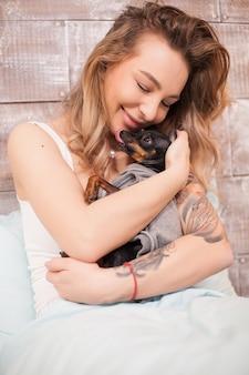 Ładna młoda kobieta w piżamie dająca uczucie jej małemu psu. szczęśliwy dorosły.