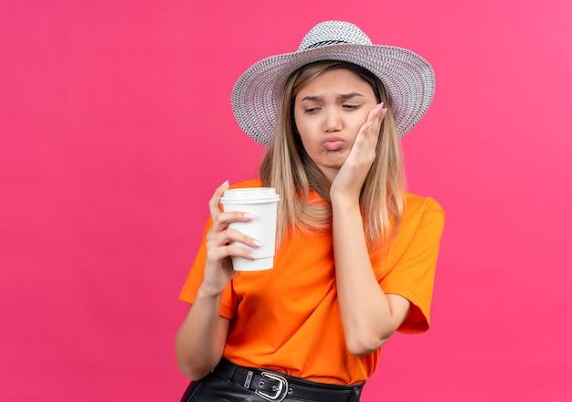 Ładna młoda kobieta w pomarańczowej koszulce w kapeluszu przeciwsłonecznym, trzymając rękę na zębach, trzymając plastikowy kubek na różowej ścianie