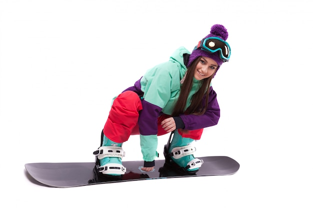 Ładna młoda kobieta w purpurowym kombinezonie narciarskim jedzie czarnego snowboard