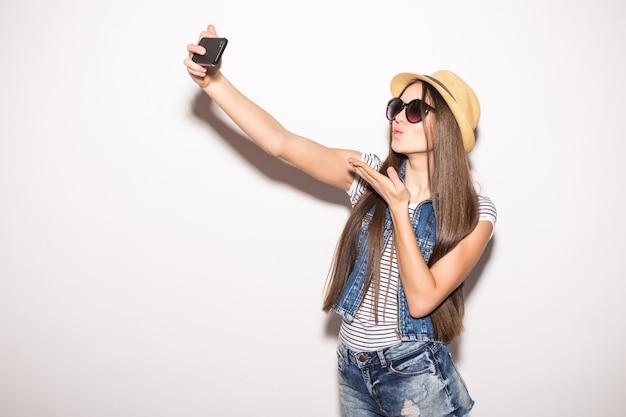 Ładna młoda kobieta w słomkowym kapeluszu i okularach przeciwsłonecznych przy selfie z telefonu komórkowego