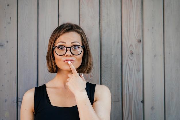 Ładna młoda kobieta w szkłach ubierał przypadkową pozycję przeciw drewnianej ścianie patrzeje rozważny, dotykający jej usta palcem wskazującym, podejmujący decyzję. masz wybór.