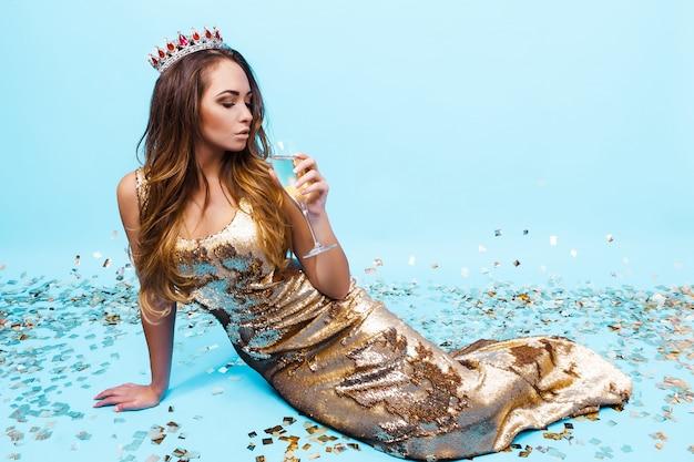 Ładna młoda kobieta w złotej sukni z szampanem