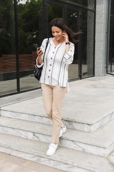 Ładna młoda kobieta w zwykłych ubraniach rozmawia przez telefon komórkowy ze słuchawkami, stojąc nad budynkiem