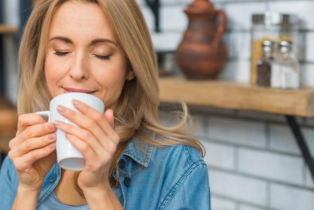 Ładna młoda kobieta wącha aromat jej kawowy napój