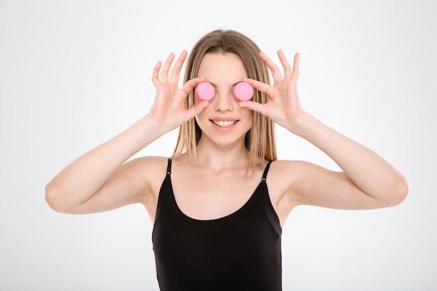 Ładna młoda kobieta włożyła makaroniki zamiast oczu