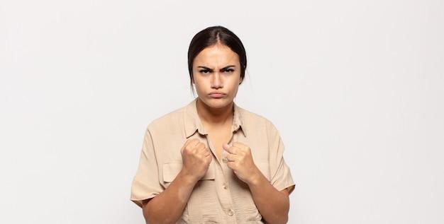 Ładna młoda kobieta wyglądająca na pewną siebie, wściekłą, silną i agresywną, z pięściami gotowymi do walki w pozycji bokserskiej