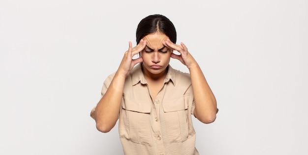 Ładna młoda kobieta wyglądająca na zestresowaną i sfrustrowaną, pracująca pod presją, bóle głowy i kłopoty