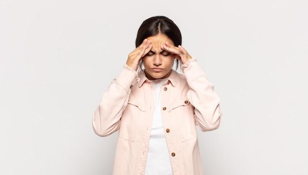 Ładna, młoda kobieta wyglądająca na zestresowaną i sfrustrowaną, pracująca pod presją, bóle głowy i kłopoty