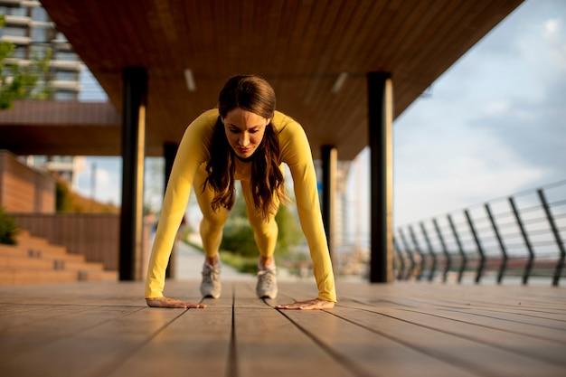Ładna młoda kobieta wykonująca pompki na drewnianym chodniku nad rzeką