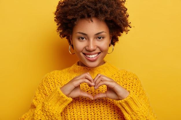 Ładna młoda kobieta wykonuje gesty miłosne, wyznaje i wyraża szczere uczucia, uśmiecha się szeroko, pokazuje równe białe zęby, nosi żółty sweter, ma delikatny wygląd