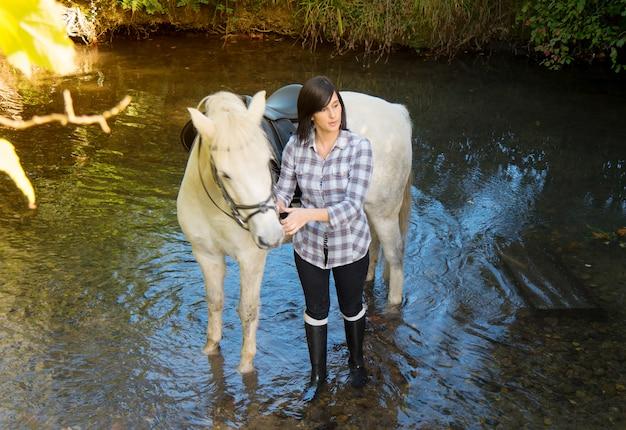 Ładna młoda kobieta z białego konia jazdą w rzece