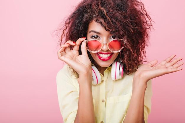 Ładna młoda kobieta z brązową skórą, trzymając różowe okulary przeciwsłoneczne i pozuje z zaskoczonym uśmiechem. kryty portret emocjonalnej afrykańskiej modelki w eleganckim żółtym stroju.