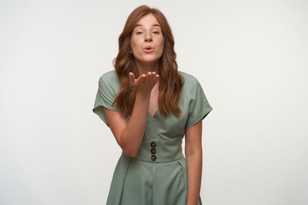 Ładna młoda kobieta z czerwonymi włosami, ubrana w pastelową sukienkę, podnosząc dłoń do twarzy i dmuchając pocałunek, odizolowane