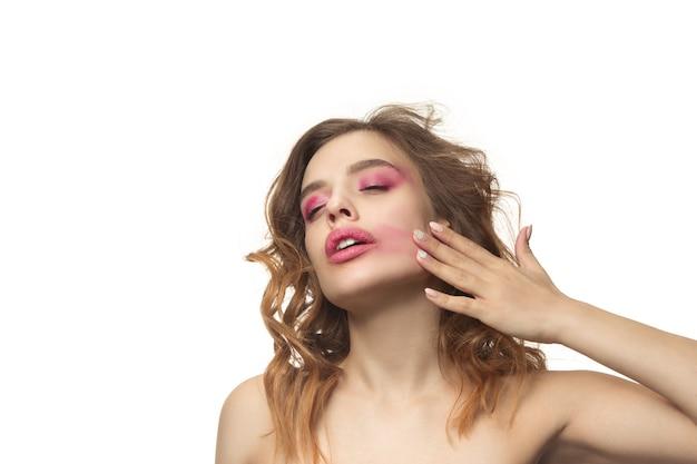 Ładna młoda kobieta z długimi falującymi jedwabistymi włosami, naturalny makijaż ręką w pobliżu podbródka na białym tle na białej ścianie. model z naturalnym makijażem.