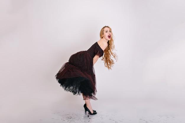 Ładna młoda kobieta z długimi kręconymi włosami, jasny makijaż, zabawy podczas sesji zdjęciowej, pozowanie. ubrana w czarną puszystą sukienkę, śliczne buty na wysokich obcasach. pełna długość..