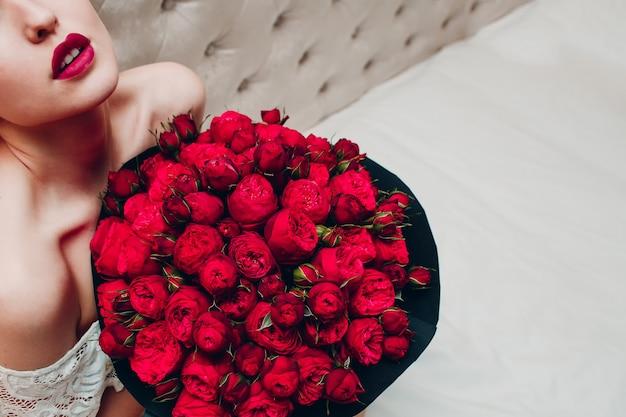 Ładna młoda kobieta z jaskrawymi błyszczącymi czerwonymi wargami i różami